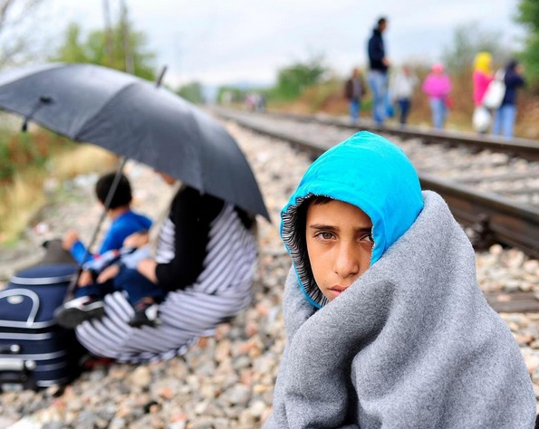 (Source: Unicef) A boy sits beside a railroad track on a rainy day in the town of Gevgelija, former Yugoslav Republic of #Macedonia, on the border with #Greece. Behind him, others who have fled their homes amid the ongoing refugee and migrant crisis walk along the tracks. Since July 2015, the rate of refugees and migrants transiting through the country has increased to up to 3,000 people per day - women and children account for nearly one third of arrivals. #refugeecrisis #migrantcrisis © UNICEF/NYHQ2015-2164/Georgiev